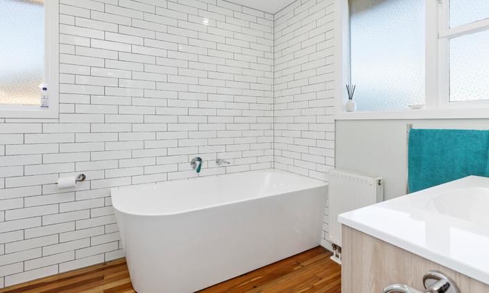 bath with tiled wall